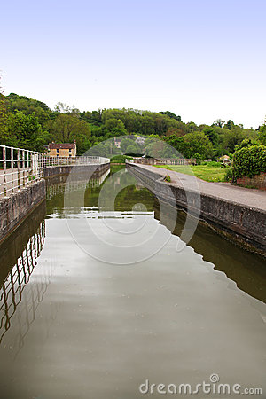 Canal boat entering lock with trees, reflection, c