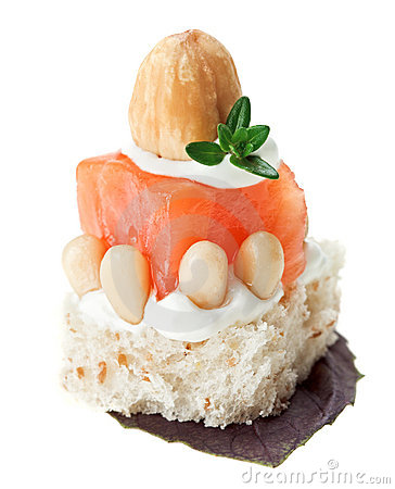 Canape with salmon, toast, thyme twig and hazelnut