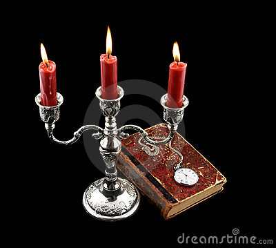 Candelabra, candles and old book with watch