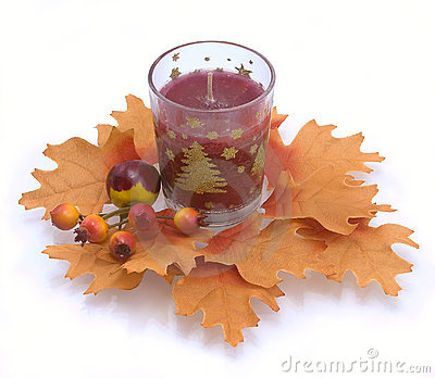 Candle in an environment of autumn leaves