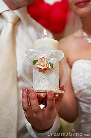 Candle in hands of newlyweds