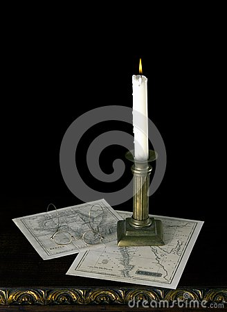 A candle with old maps  in old candlestick on old