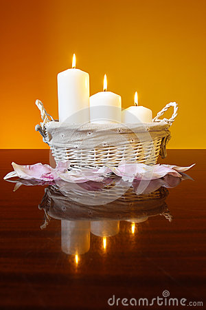 Candles in basket on orange background
