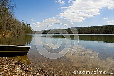 Canoe at edge of peaceful lake