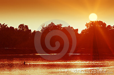 Canoeing man silhouette on a lake