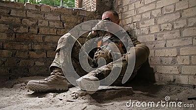 Cansado después del soldado del ejército de la batalla que se sienta en la tierra almacen de video