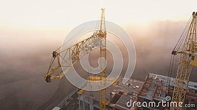 Canteiro de obras na névoa com um olho do ` s do pássaro com os guindastes de torre no por do sol filme