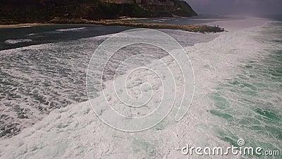 Cantidad aérea de la cámara lenta del abejón de las olas oceánicas que se rompen antes de la orilla Bali, Indonesia almacen de metraje de vídeo
