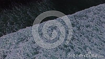 Cantidad aérea del abejón de las olas oceánicas que se rompen antes de la orilla en puesta del sol Bali, Indonesia metrajes