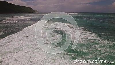 Cantidad aérea del abejón de las olas oceánicas que se rompen antes de la orilla en puesta del sol Bali, Indonesia almacen de video