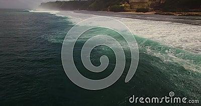Cantidad aérea del abejón 4k de las olas oceánicas que se rompen antes de la orilla Bali, Indonesia almacen de video
