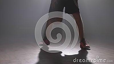 Cantidad cercana de las piernas del ` s del jugador de básquet que juegan con la bola en sitio brumoso oscuro con humo almacen de metraje de vídeo
