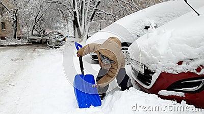 cantidad 4k de las nieves acumulada por la ventisca de excavación sonrientes felices del niño pequeño en el aparcamiento con la p almacen de video