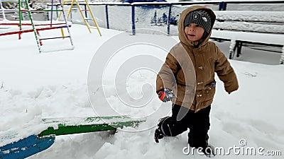 cantidad 4k del niño pequeño que camina y que sube sobre la nieve acumulada por la ventisca en el patio en el parque después de t metrajes
