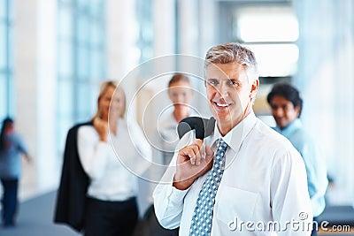 Cappotto della holding dell uomo di affari maturi sopra la sua spalla