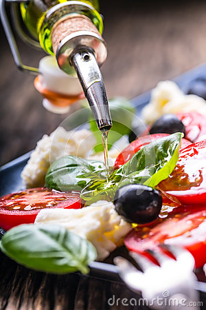 Free Caprese Salad.Mediterranean Salad. Mozzarella Cherry Tomatoes Basil And Olive Oil On Old Oak Table. Italian Cuisine Stock Photos - 92784163