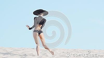 Captura de vista trasera de una bailarina atlética que actúa al aire libre en la arena almacen de metraje de vídeo