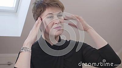 Capture d'écran de la charmante brunette regardant dans le miroir et touchant son visage Caucasienne mûre inquiète banque de vidéos