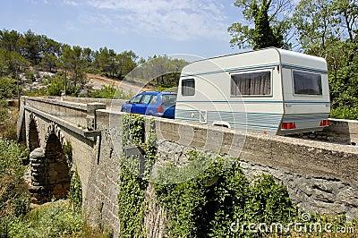 Car with caravan at bridge
