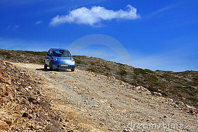 The car on a dirt road on a mountain slope. Greece