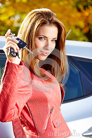 Car driver woman showing new car keys and car.
