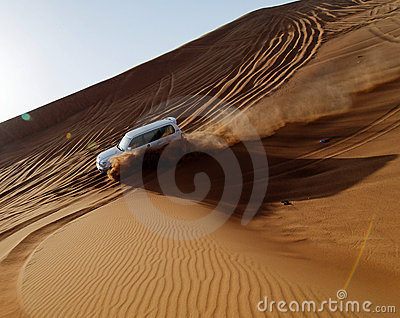 Car driving down sand dune