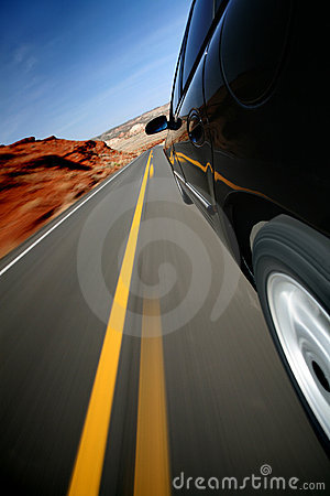 Car driving on rural road with motion blur
