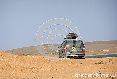 A car is driving through sands