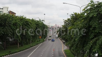Car driving to and from base of Phra Pinklao bridge with trees, Bangkok stock video