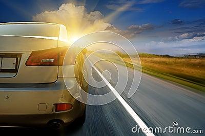 Car driving towards sunshine
