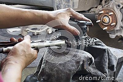 Car mechanic fixing parts of automobile