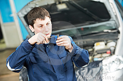 Car mechanic inspecting engine sparking plug