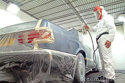 Car mechanic and paint spray