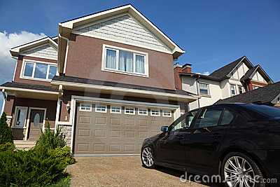 Car near garage of new two-storied cottage