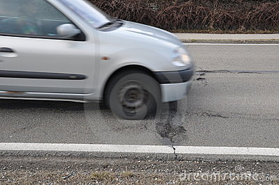 Car and pothole on road