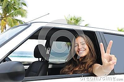 Car rental: happy woman in her car near the beach