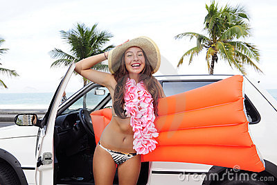 Car rental: happy woman and her car near the beach