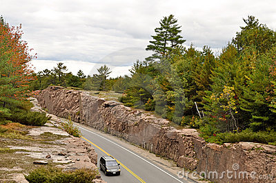 Car on a road through a rock cut