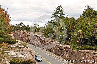 Car on a road through a rock cut