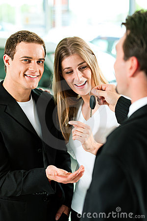 Car sales - key being given to couple