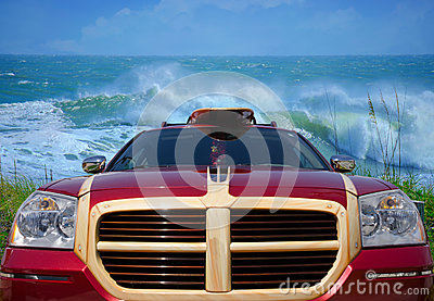 Car with surfboard at beach with big waves