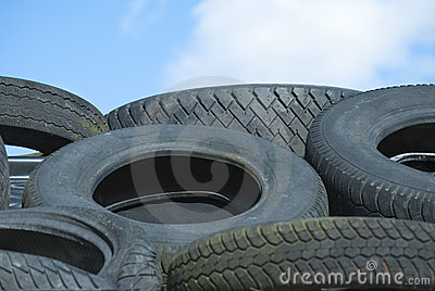 Car Tyres in Recycle Pile against Blue Sky