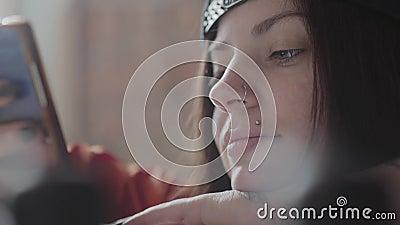 Cara ascendente próxima de uma jovem mulher com bordo e anel perfurados no nariz que texting no telefone celular Menina incomum b vídeos de arquivo