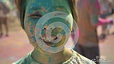 A cara da menina asiática feliz nova está sorrindo com pó colorido no festival do holi no dia no verão, conceito da cor video estoque