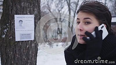 Cara de escolta de una bella joven caucásica hablando en un smartphone con el anuncio de su hijo desaparecido en segundo plano Ni almacen de video