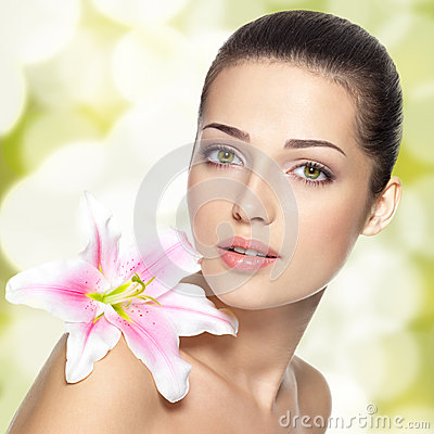 Cara de la belleza de la mujer joven con la flor. Concepto del tratamiento de la belleza