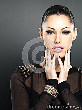 La cara de la mujer de la moda con los clavos negros y brillantes hermosos hacen