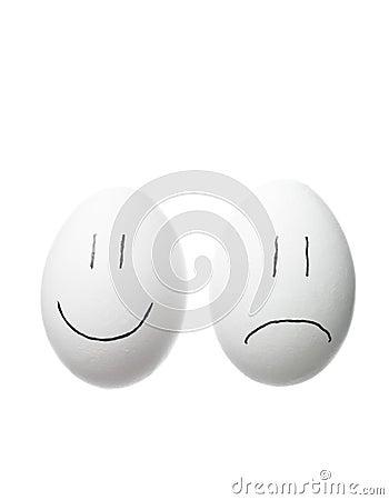Cara triste y una cara feliz pintada en los huevos blancos