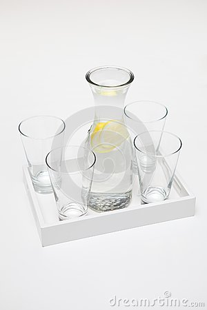 Carafe of lemon water and four glasses.