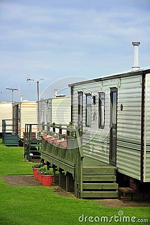 Caravan camp on green grass under clouds
